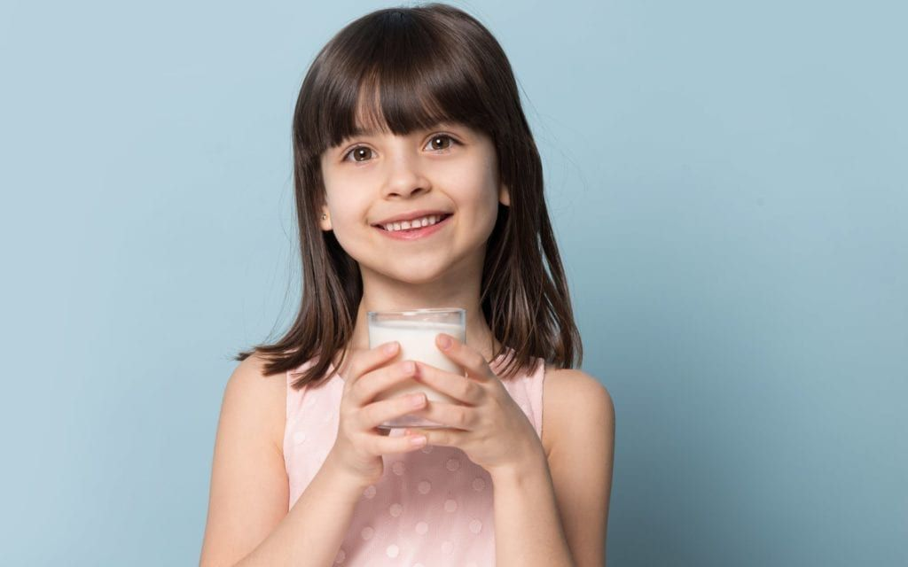 Child holding glass of milk and smiling