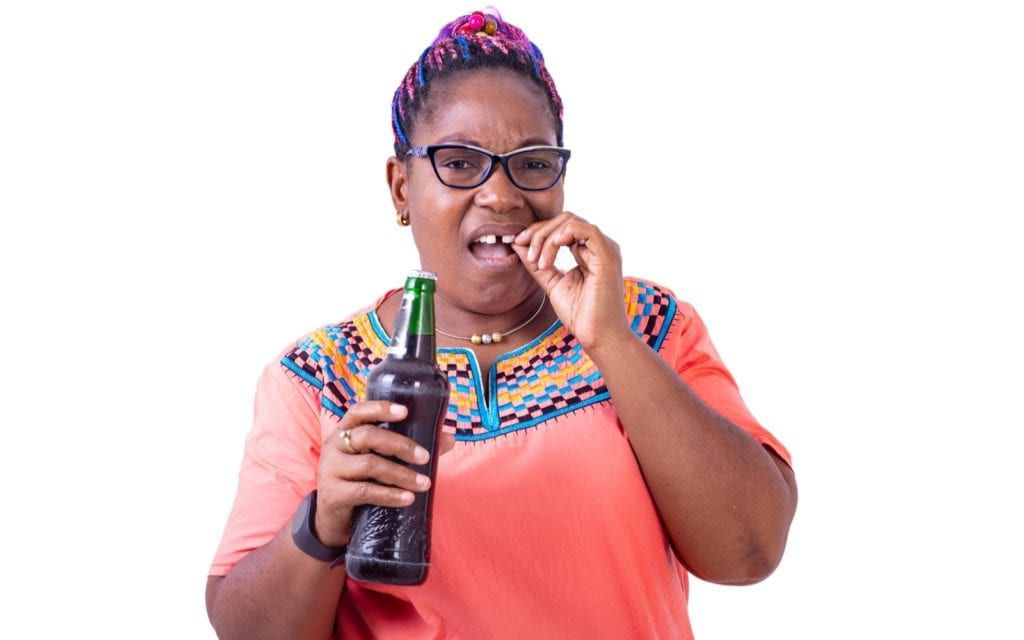 African Woman Holding Bottle With Tooth Pain